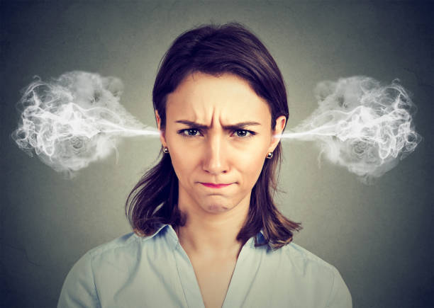 angry young woman, blowing steam coming out of ears stock photo