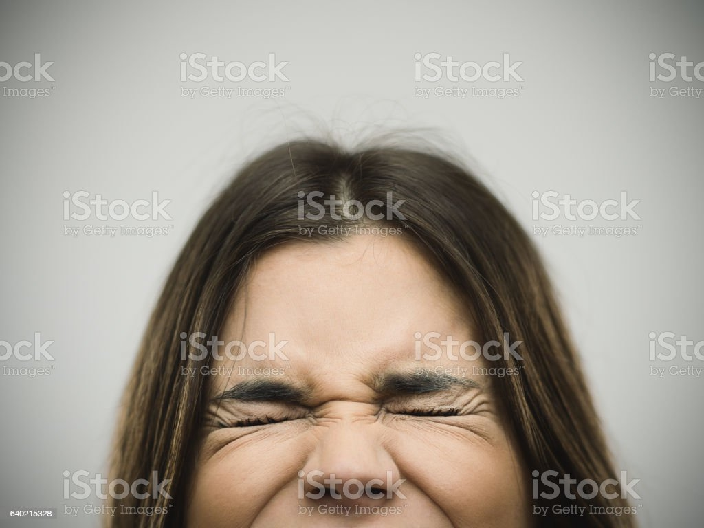 Angry young woman clenching eyes stock photo