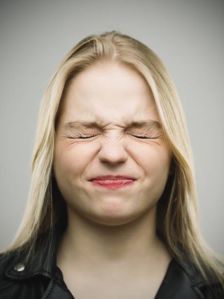 Angry young woman clenching eyes - Photo
