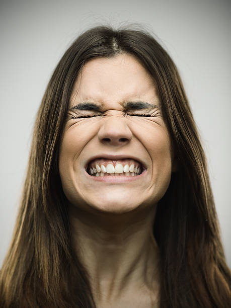 Angry young woman clenching teeth Close-up of angry young woman clenching teeth. Aggressive female is with eyes closed. She is against gray background. Vertical studio photography from a DSLR camera. Sharp focus on eyes. grimacing stock pictures, royalty-free photos & images