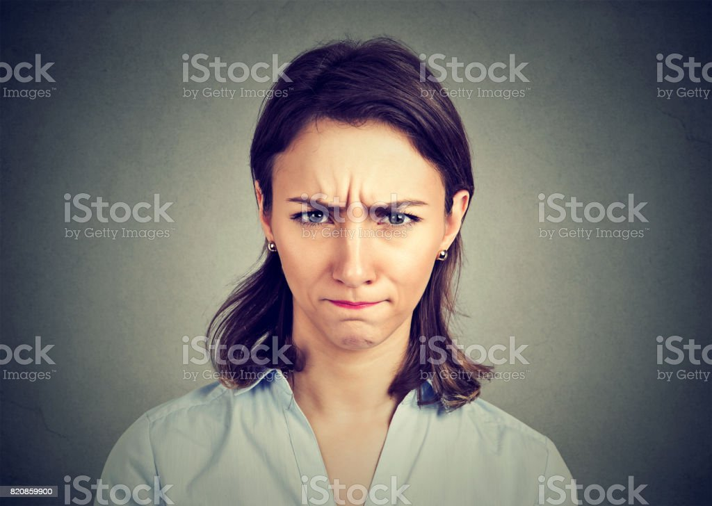 Angry young woman isolated on gray background. stock photo