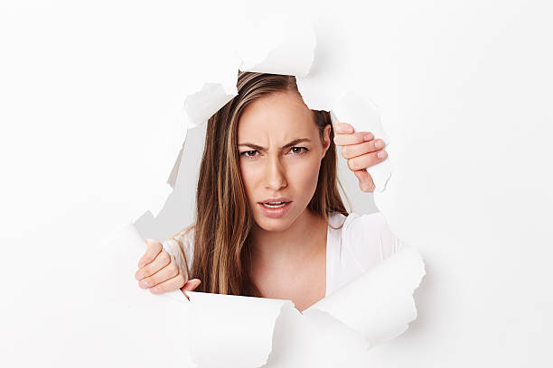 Angry young woman looking through torn paper, portrait stock photo