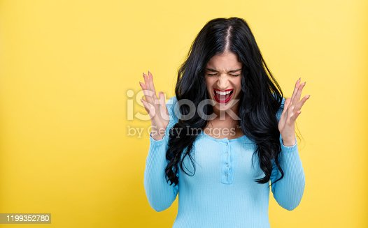Angry young woman on a yellow background