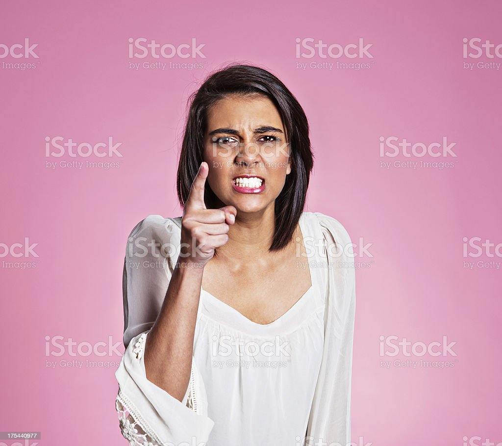 Angry young woman points an accusing finger and frowns royalty-free stock photo