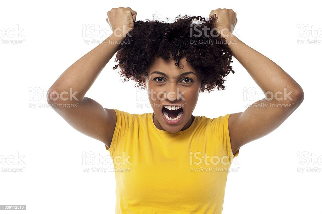 Angry young woman pulling her hair out stock photo