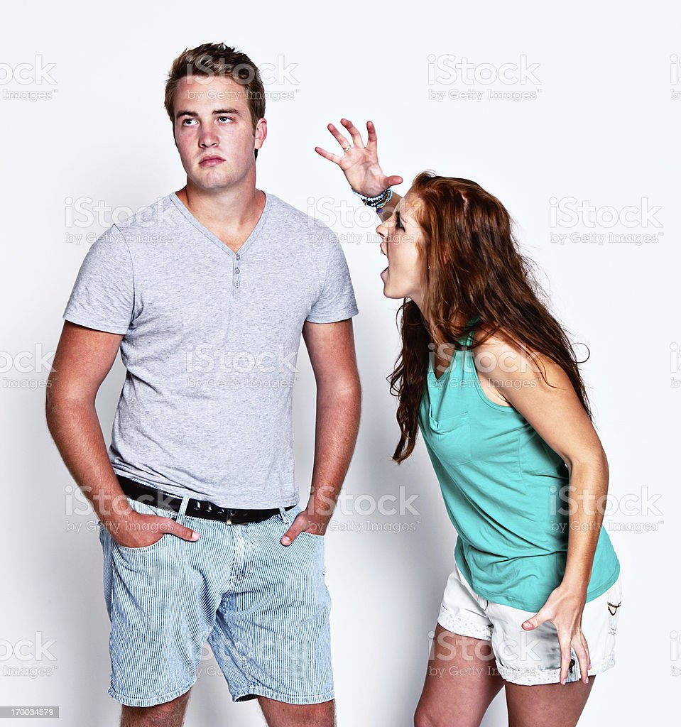 Angry young woman screaming at her bored uncaring boyfriend stock photo