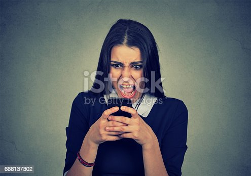 824614192istockphoto angry young woman screaming on mobile phone 666137302