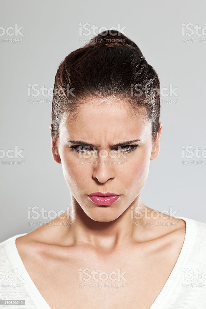 Angry young woman, Studio Portrait Portrait of angry young woman staring at the camera. Studio shot on a grey background. 20-24 Years Stock Photo