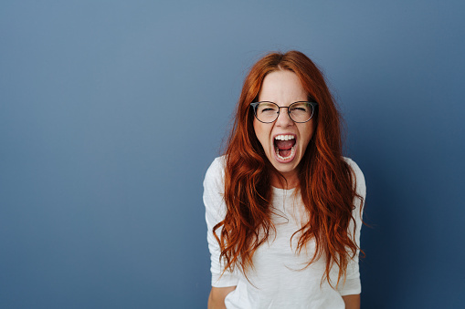 Angry young woman throwing a temper tantrum yelling at the camera with a furious expression over a blue studio background with copy space