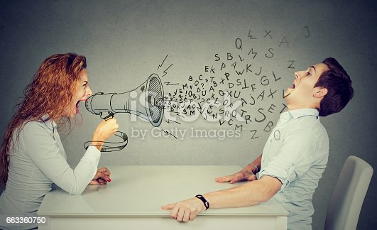 istock angry young woman with megaphone shouting at stressed scared man blown away by wave of alphabet letters 663360750