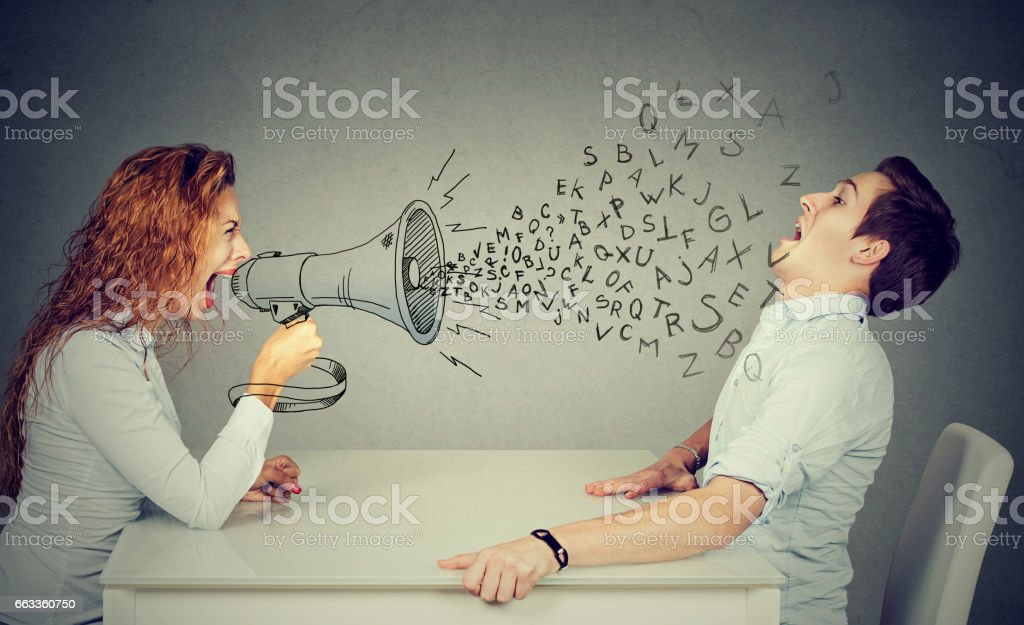 angry young woman with megaphone shouting at stressed scared man blown away by wave of alphabet letters stock photo