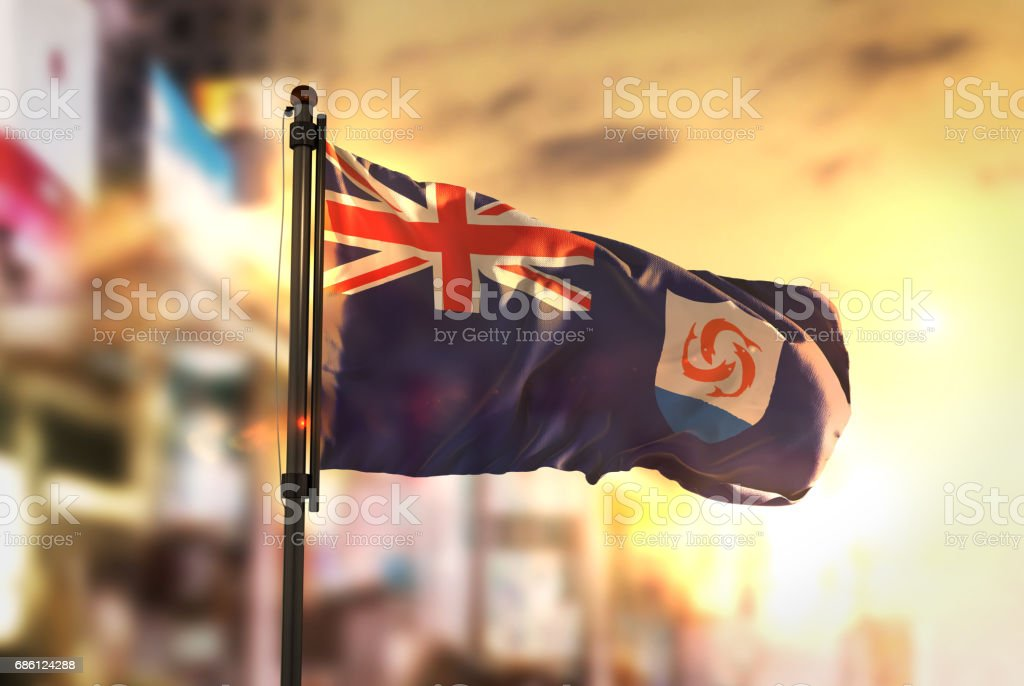 Anguilla Flag Against City Blurred Background At Sunrise Backlight stock photo