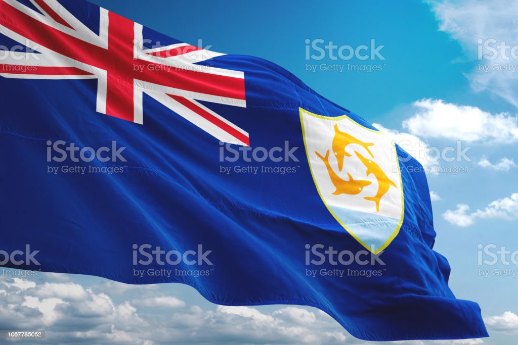 Anguilla flag waving isolated cloudy sky background stock photo