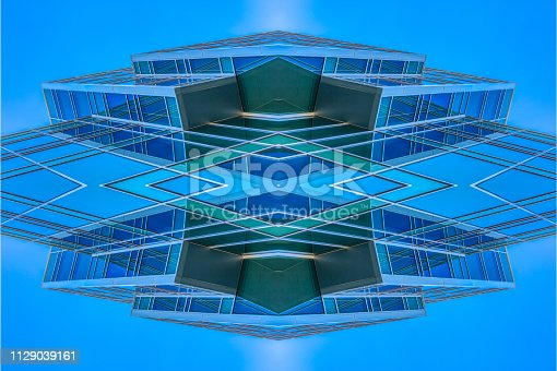 istock Angular building looking abstract with sky reflect 1129039161