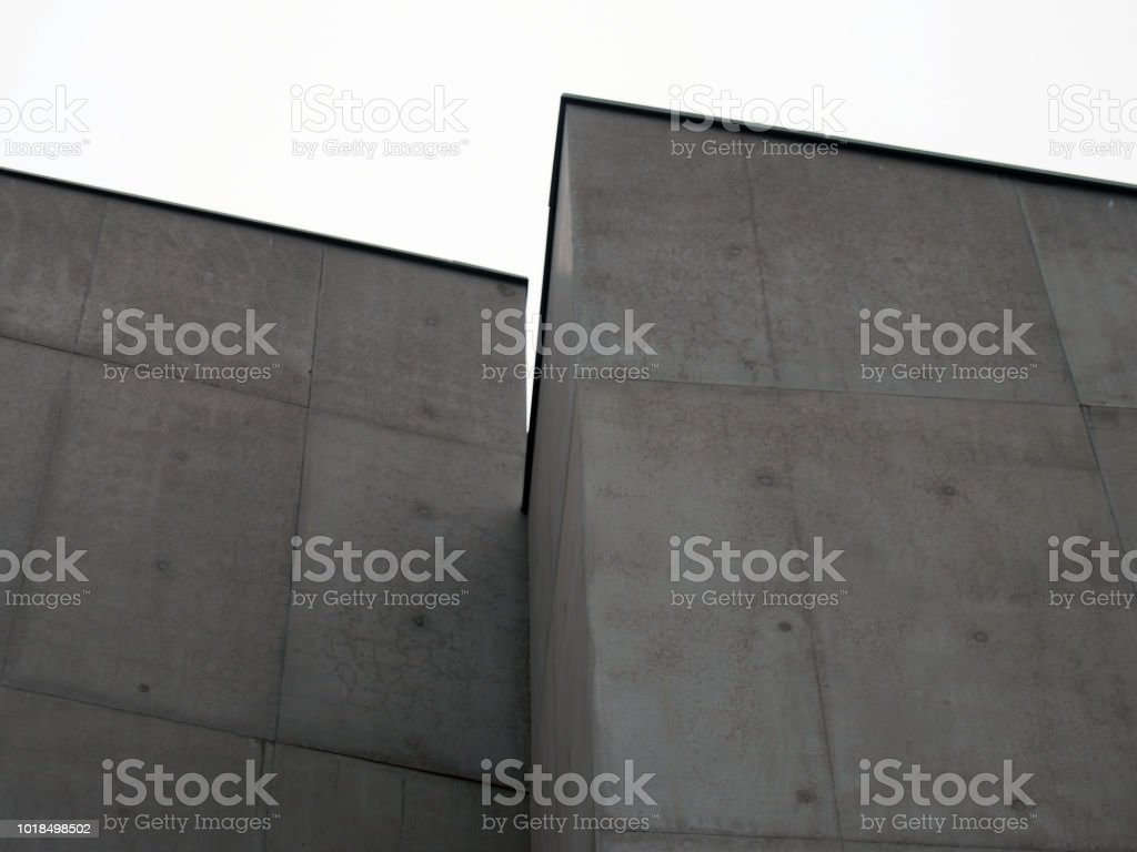 angular stark concrete walls with corners and white sky with rectangular panels and regular marks stock photo