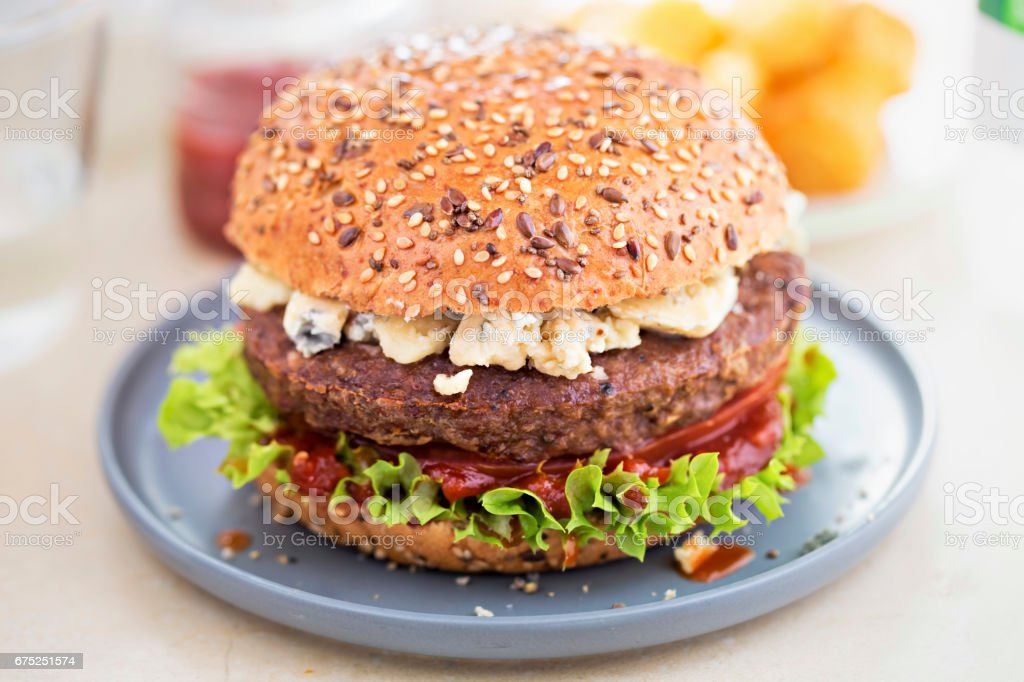Angus burger on grain bun with tomato relish, lettuce and blue cheese stock photo