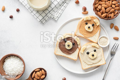 Animal face breakfast toasts with nut butter for kids on concrete background with copy space for text. Food art, kids menu or healthy vegan snack for children concept