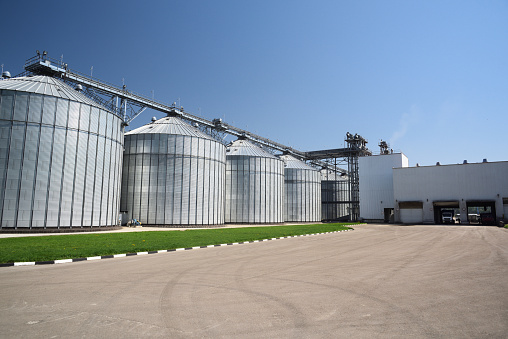 Animal feed factory. Big modern granary in sunny summer day. Metal containers for grain horizontal