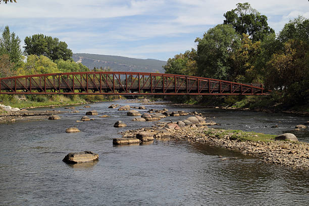 Animas River in Durango, Colorado View of Animas River in Durango with footbridge crossing the river. Photo taken September 28, 2015. Shoreline and rocks in the river show residue from August 5, 2015 accidental gold mine wastewater release up stream in Silverton, Colorado.  animas river stock pictures, royalty-free photos & images