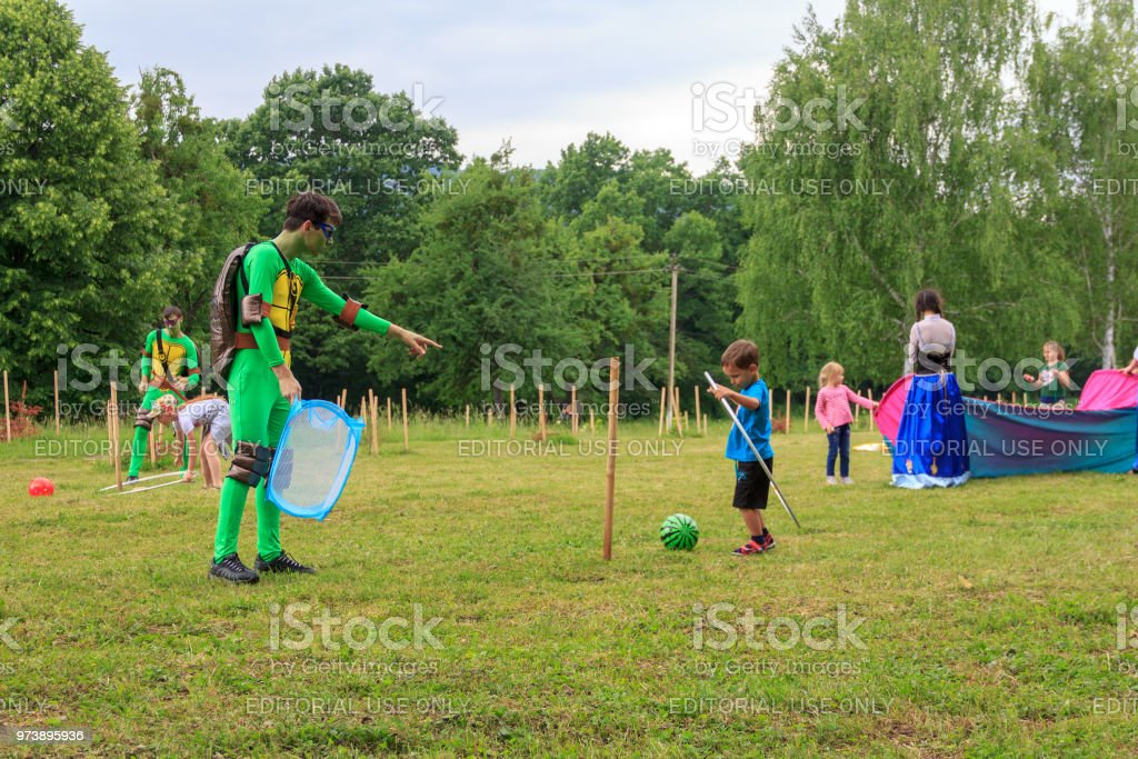 Animators play with children in outdoor games on a children's holiday on a summer day in Adygea стоковое фото