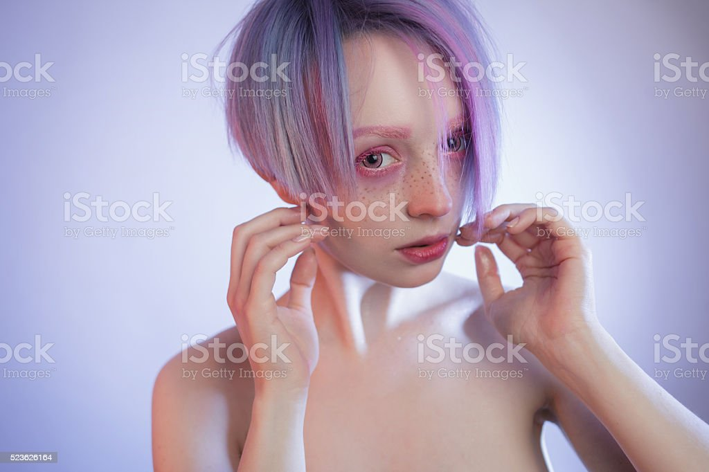 Anime. Hands on face, young girl with pink eyes and stock photo