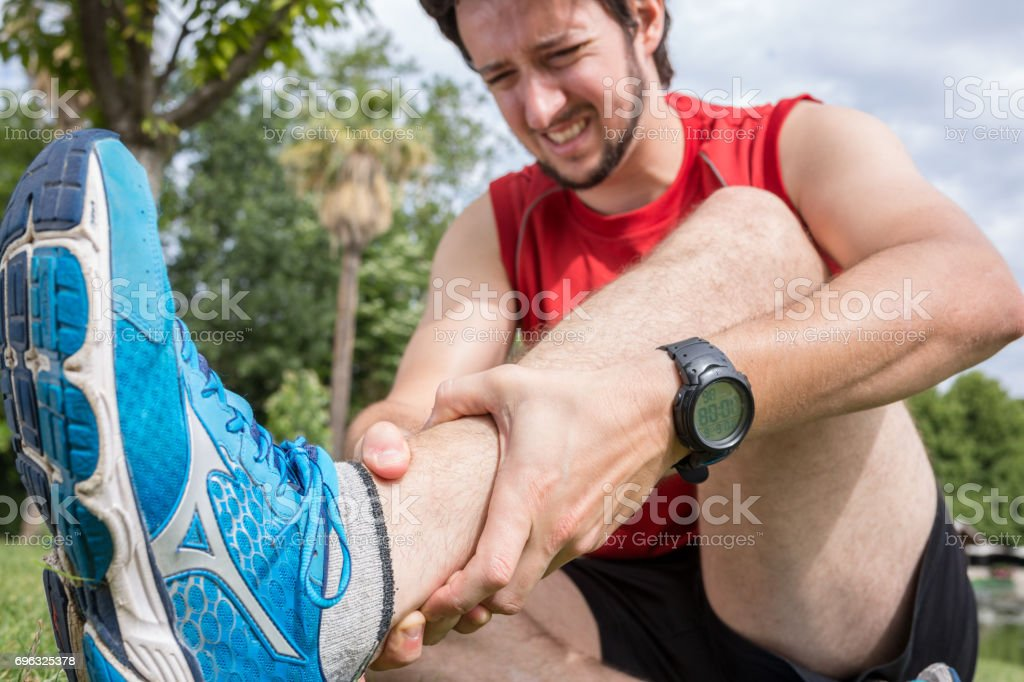 Ankle injury while jogging in the park, The man has wrong stock photo