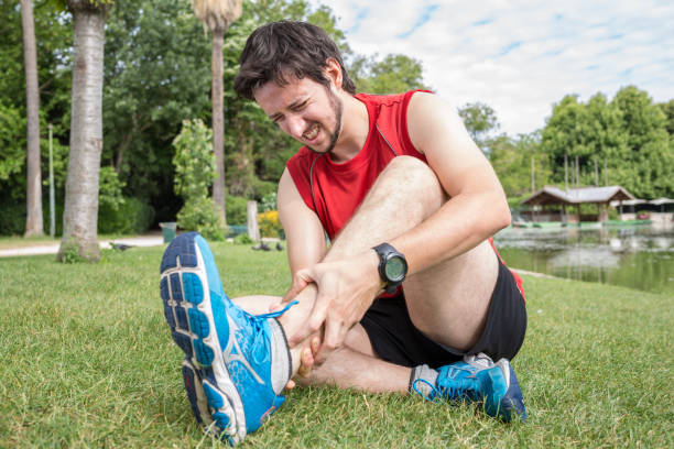 ankle injury while jogging in the park, the man has wrong - slogatura foto e immagini stock