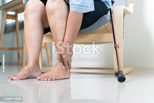 875123630 istock photo Ankle leg pain of senior woman at home, healthcare problem of senior concept 1258974936