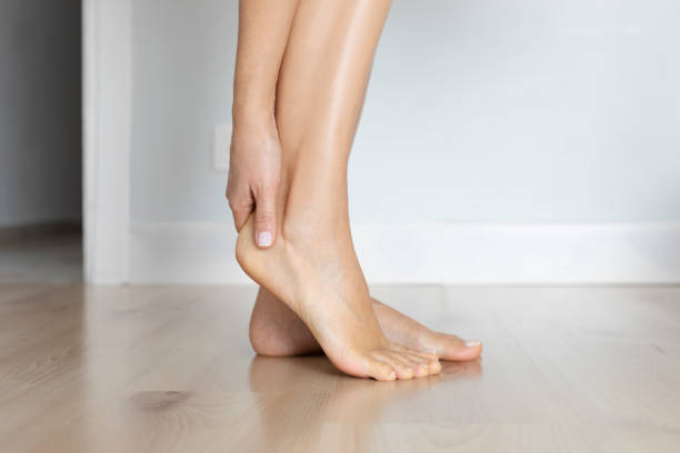 Ankle Pain Female is holding her ankle out of pain at home. podiatry stock pictures, royalty-free photos & images