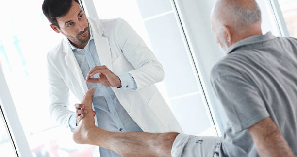 ankle sprain examination. - old man feet stock photos and pictures