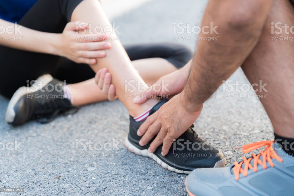 Ankle sprained. Young woman suffering from an ankle injury while exercising and running and she getting help from man touching her ankle. stock photo