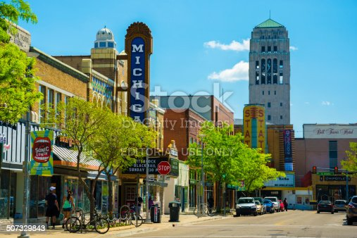 Ann Arbor, United States - May 25, 2014: Scene from Downtown Ann Arbor, Michigan, with shops, pedestrians walking, a theater, and a bell tower from the University of Michigan being shown.