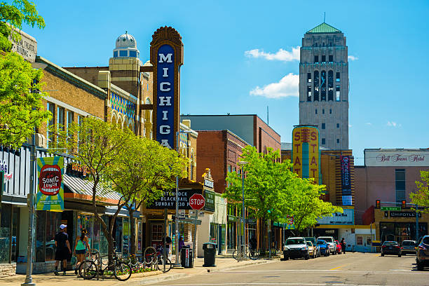 Ann Arbor Downtown Scene Ann Arbor, United States - May 25, 2014: Scene from Downtown Ann Arbor, Michigan, with shops, pedestrians walking, a theater, and a bell tower from the University of Michigan being shown. ann arbor stock pictures, royalty-free photos & images