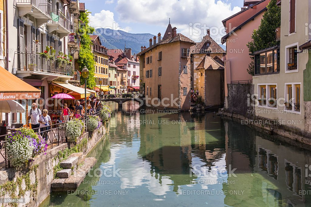 Annecy, France. Building facades on a canal and tourists walking stock photo
