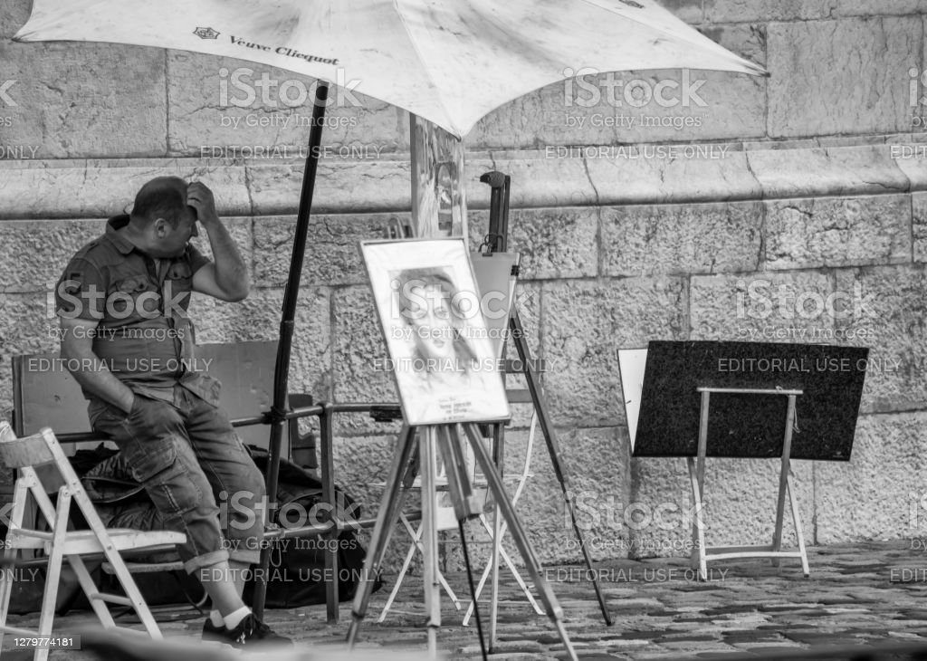 Annecy, France Street artist next to the canal in Annecy, France. He is looking bored as he has no customers despite an example of his work being displayed on an easel. 2019 Stock Photo