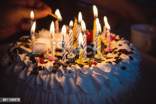 istock anniversary cake with hand burning candles in dark 891158978