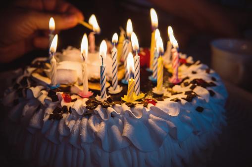 istock anniversary cake with hand burning candles in dark 891158978