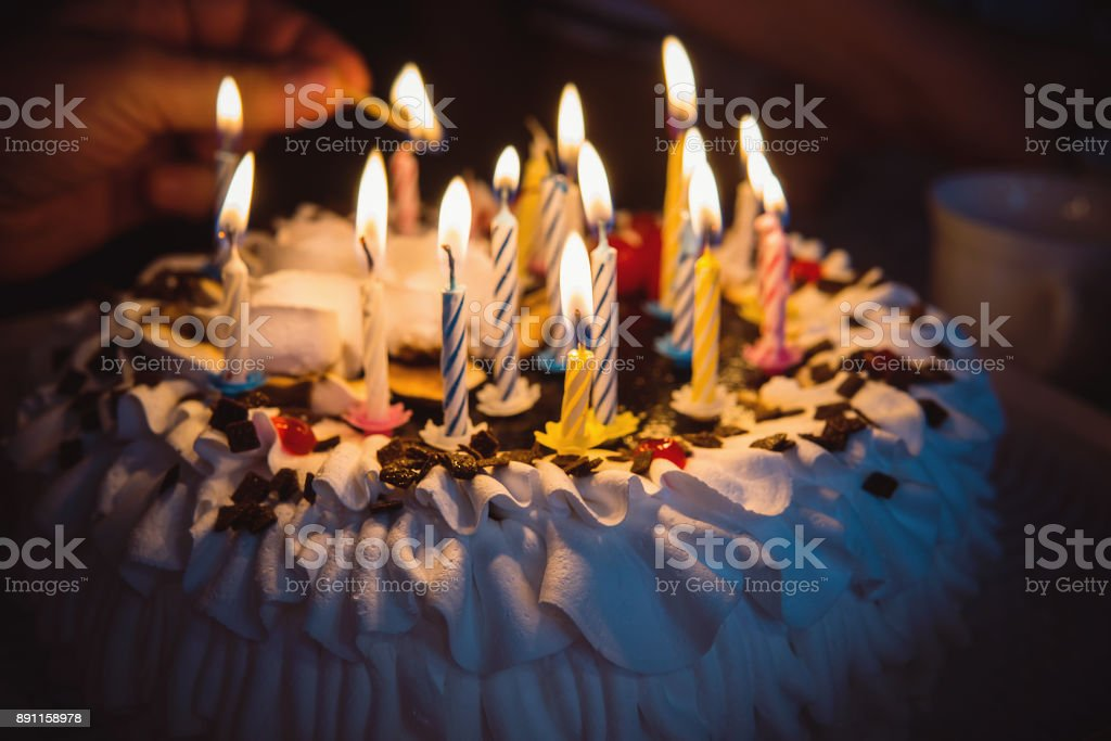 anniversary cake with hand burning candles in dark stock photo