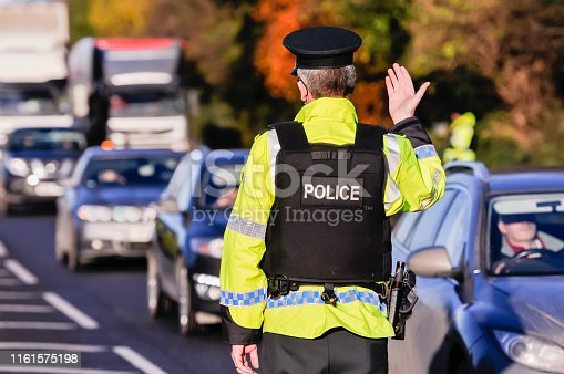 Belfast, Northern Ireland. 24 Nov 2016 - An armed PSNI officer waves on traffic during a vehicle checkpoint.