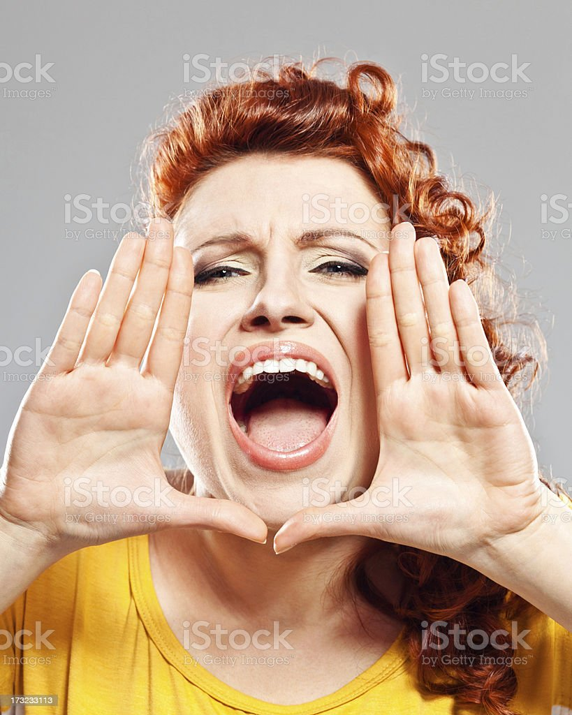 Announcement Portrait of young woman, screaming at the camera. Studio shot, grey background. 25-29 Years Stock Photo
