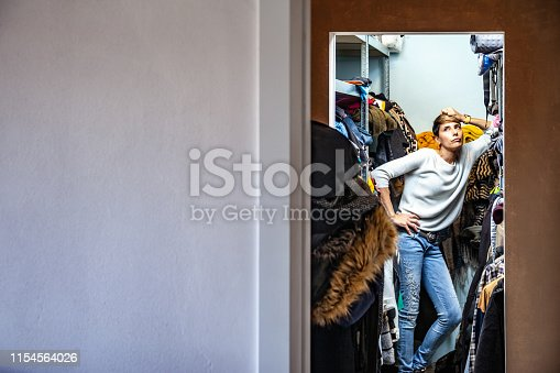 Annoyed Adult Woman Leaning on a shelf in her Closet