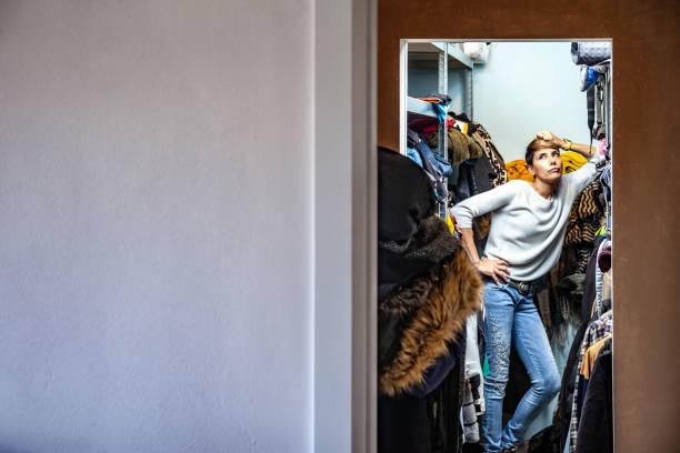 Verärgert erwachsene Frau, die in ihrem Schrank auf einem Regal steht – Foto