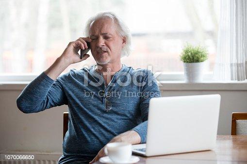 865714662 istock photo Annoyed aged man having unpleasant phone talk 1070066650