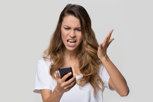 istock Annoyed angry woman mad about stuck phone isolated on background 1126440404