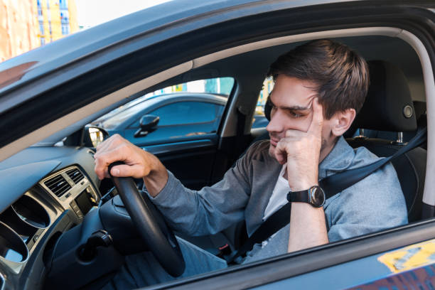 Annoyed buisnessman in car late for meeting stock photo