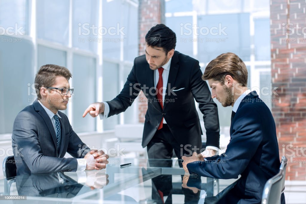 annoyed businessman scolds his employees stock photo