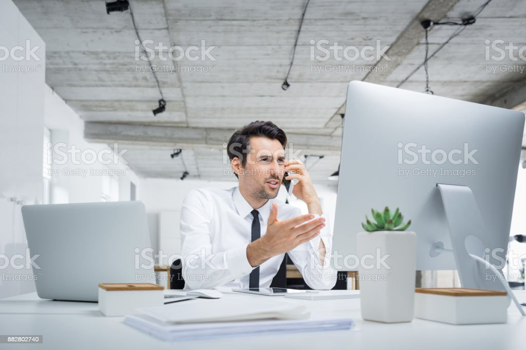 Annoyed businessman talking on phone in office stock photo