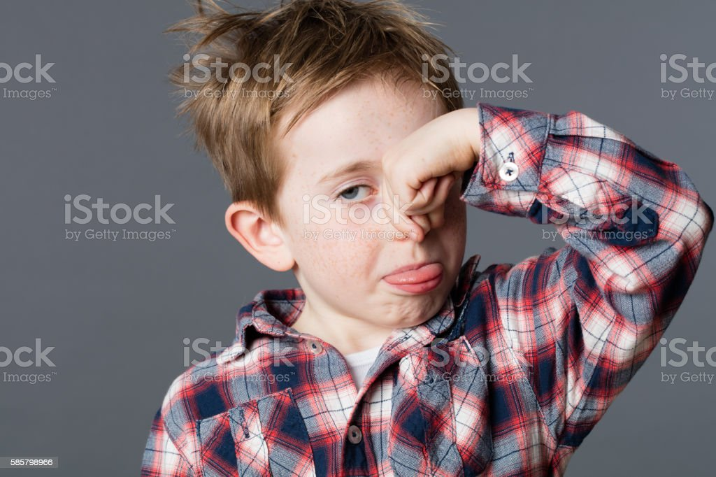 annoyed child pinching his nose for smell, sticking out tongue stock photo