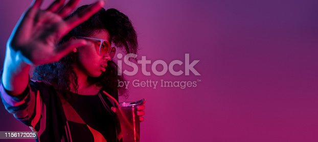 istock Annoyed fashion young african girl black woman wear stylish pink glasses hold drink say no refuse with stop hand gesture isolated on party purple studio background, banner website design, copy space 1156172025