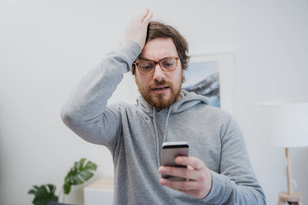 Annoyed frustrated male reading bad news on the cellphone stock photo